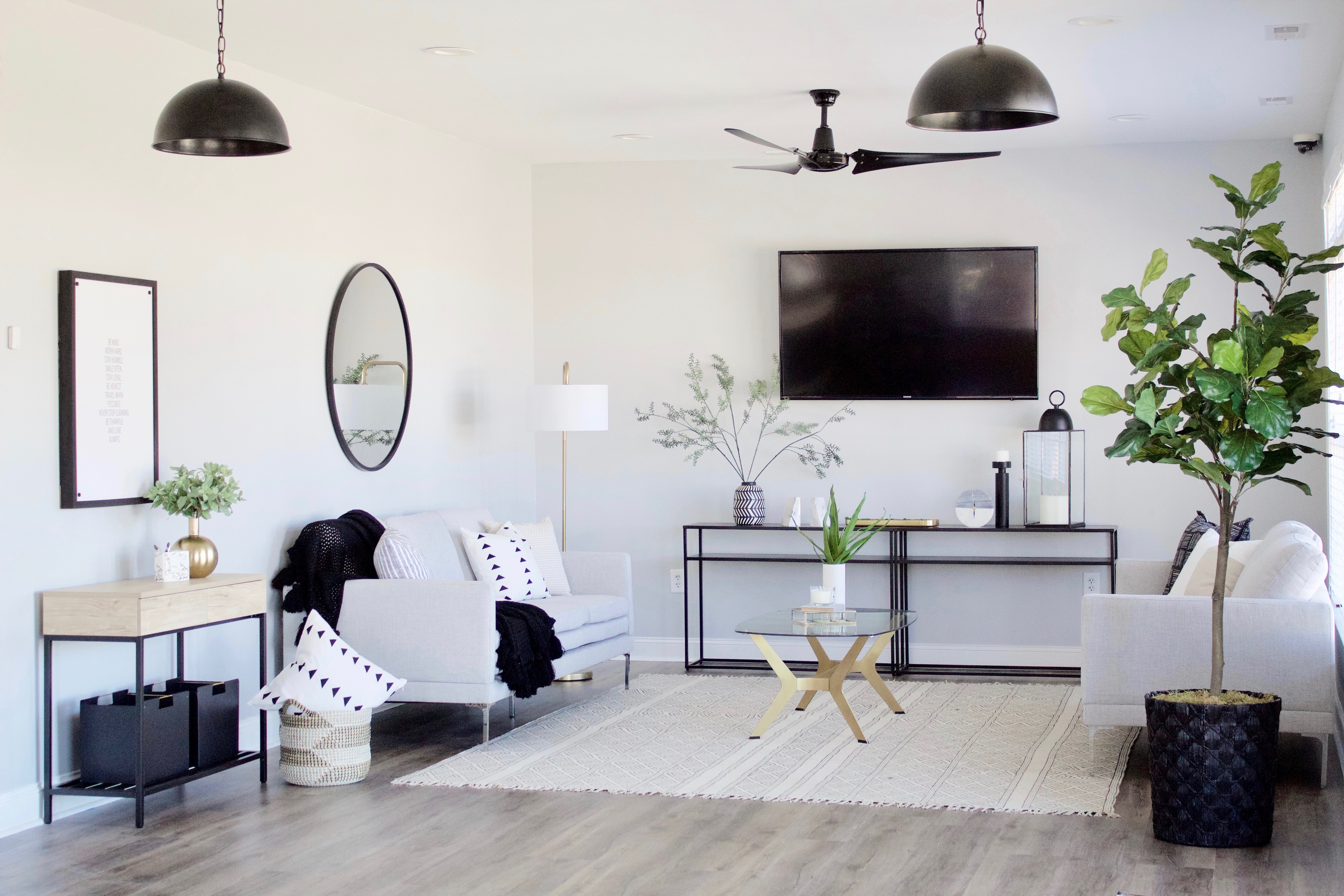A bright modern lounge featuring light grey walls and sofas accented by black details and light woods.