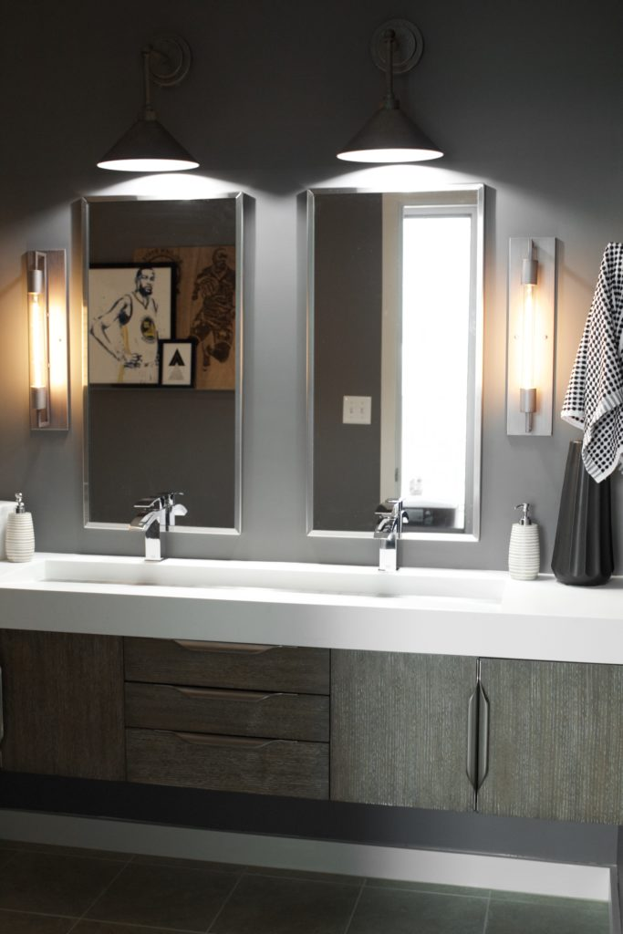 "Our Encore Condo project features a modern masculine owner's bathroom with a wall-mounted double floating vanity and 4"" thick integrated matte white trough sink against dark gray walls. #modernmasculine #ownersbathroom #condobathrooms #BehrAsphaltGray"