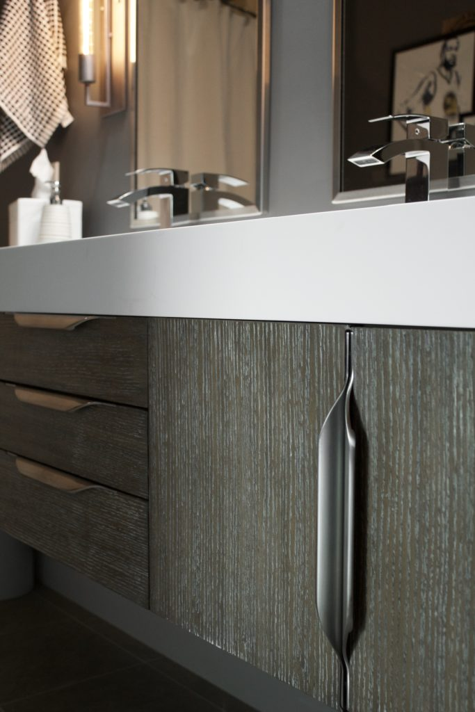 """Our Encore Condo project features a modern masculine owner's bathroom with a wall-mounted double floating vanity and 4"""" thick integrated matte white trough sink against dark gray walls. #modernmasculine #ownersbathroom #condobathrooms #BehrAsphaltGray"""