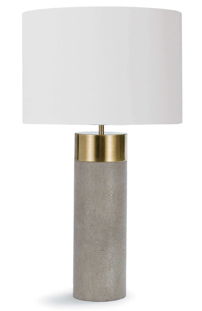 Boasting a fabric drum shade atop a column base with a faux shagreen facade and brass band, this lamp beautifies while it illuminates. It also features a 3-way turn knob to allow for creating multiple levels of light to complement a mood or a task.
