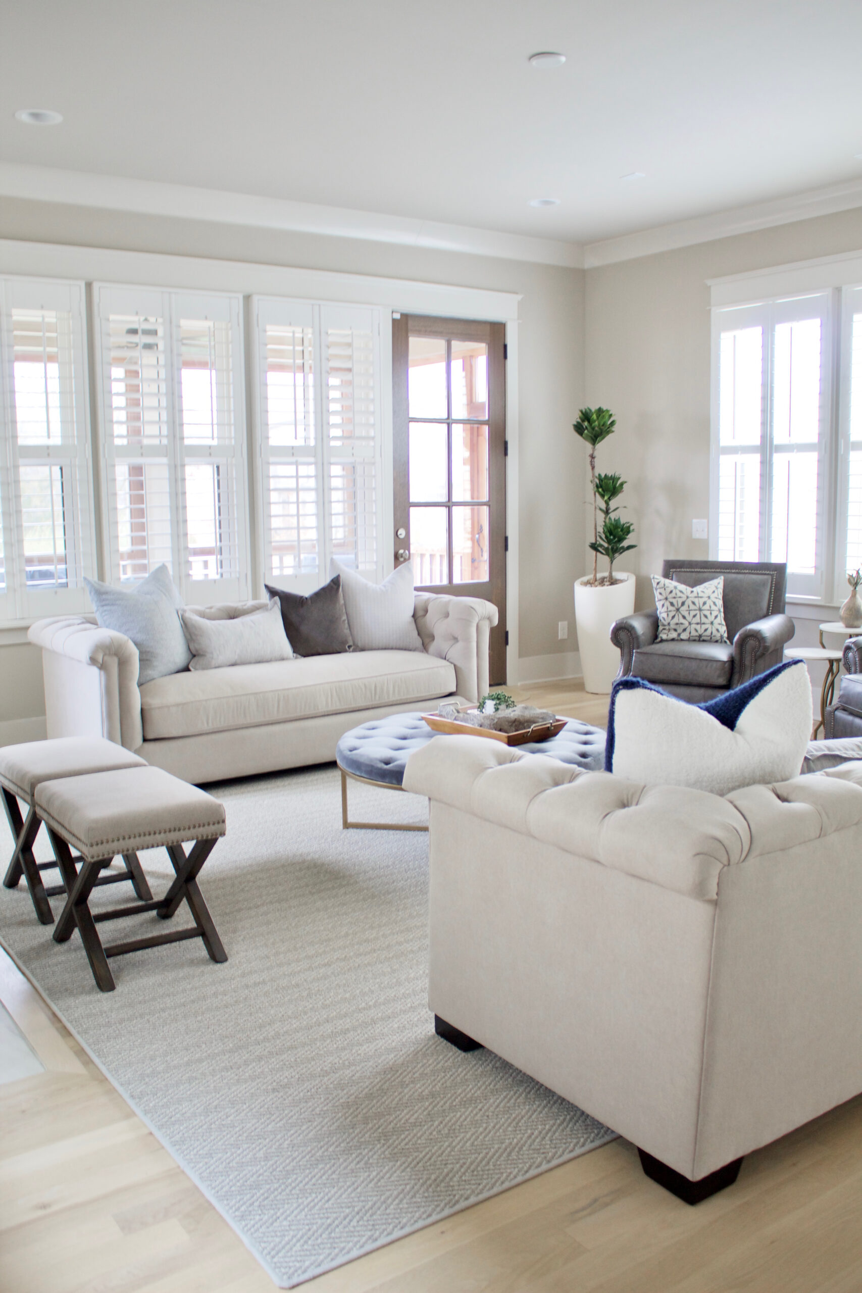 A light gray tufted sofa with traditional influence and modern flare. As part of the Kelly Clarkson Home Collection, it features a tufted back with matching roll arms and a bench-style cushion. The velour upholstery adds a welcoming, luxe element that makes it perfect for a contemporary living space. #lightgraysofa #lightgraytuftedsofa #tuftedsofa #contemporarytuftedsofa #benchseatsofa #KellyClarksonHomeCollection