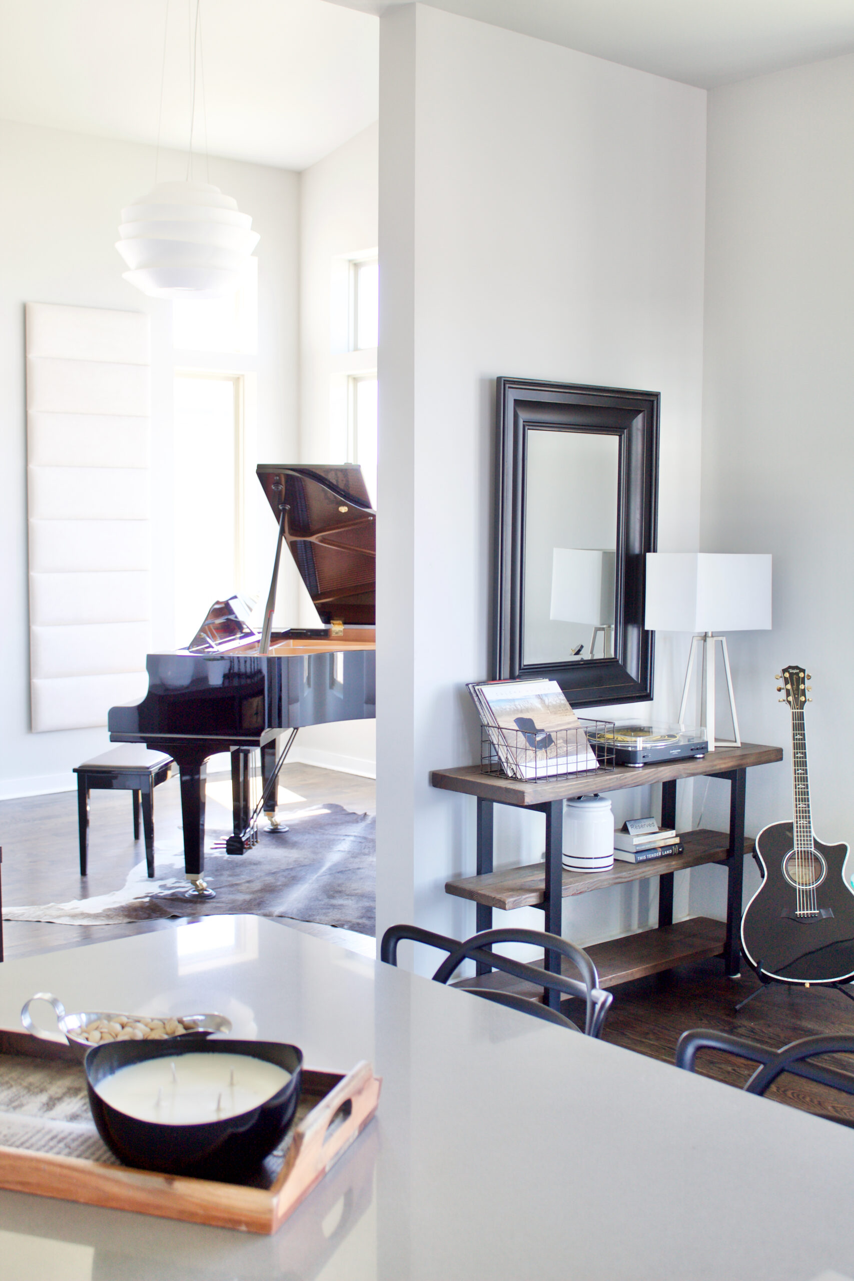 The foyer of our #MinimalModernSouthNashville project features modern entry lighting suspended over a baby grand piano with large windows on three walls and a sloped ceiling that reaches 15'H. The spherical pendant is made of white bands that diffuse the light and create a soft, dimensional glow. Light is also projected directly upward and downward to dramatically highlight the space, making it the perfect welcoming statement piece. Interior wall and ceiling color is Sherwin Williams Repose Gray SW 7015. The trim is bright white. #SherwinWilliamsReposeGrayInteriorWalls #ReposeGraySW7015 #interiorpaintcolor #lightgrayinteriorpaintcolors