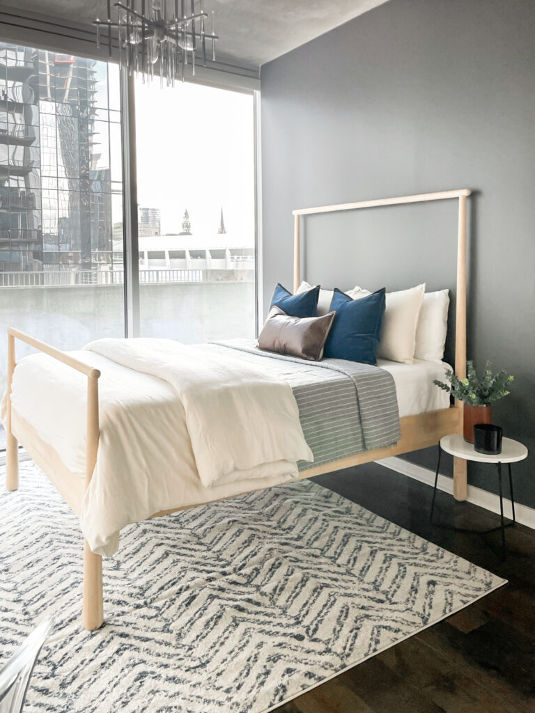 Our Encore Condo Project is located in downtown Nashville, Tennessee. The guest bedroom has a wall of floor-to-ceiling windows overlooking Bridgestone Arena and surrounding high-rise buildings. We transformed the space into a multi-functional room that accommodates all of their requests by adding a custom wall-to-wall built-in cabinet and updated furnishings. #guestbedroom #whitebuiltins #BehrAsphaltGray