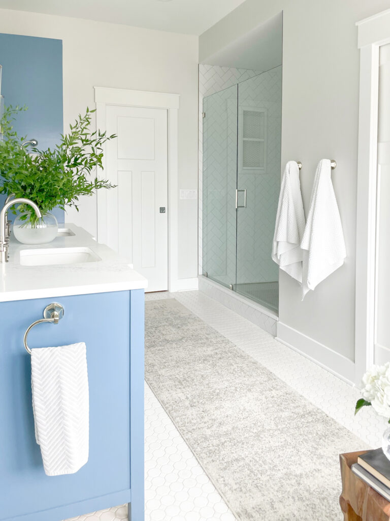 A primary bathroom design featuring classic and contemporary elements. The custom blue vanity including a linen closet is balanced by white quartz countertops, light gray walls, and white tile. #SherwinWilliamsReservedWhite #BenjaminMooreLazySunday #BlueBathroomVanity #PaintColor #LightGrayBathroomWallsWithBlueVanity #dbCPHistoricEdgefieldProject